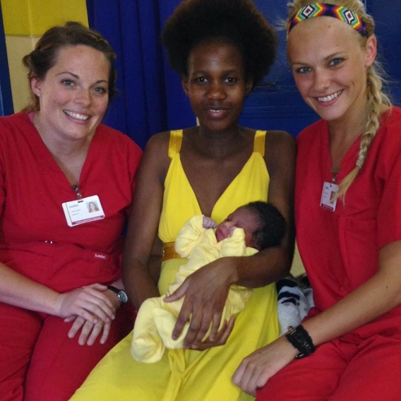 Two IU nursing students pose with a woman and her newborn baby at a hospital in Swaziland.