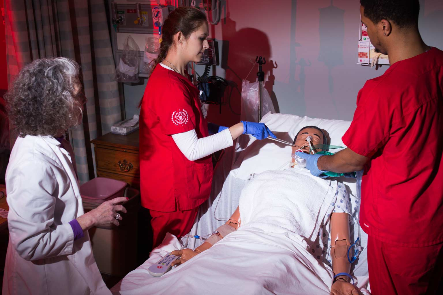 IU nursing students practice patient care skills on a medical manikin while an instructor observes.