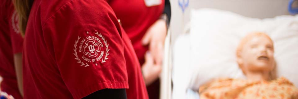 A nursing student wears scrubs that display the IU School of Nursing sigillum.