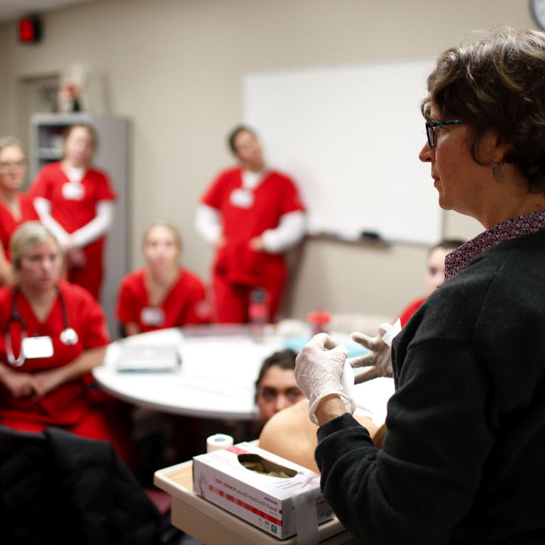 A School of Nursing faculty member gives a demonstration to a class.