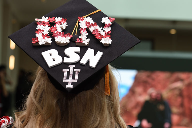 A student wears a graduation cap that is decorated to say 'RN BSN.'
