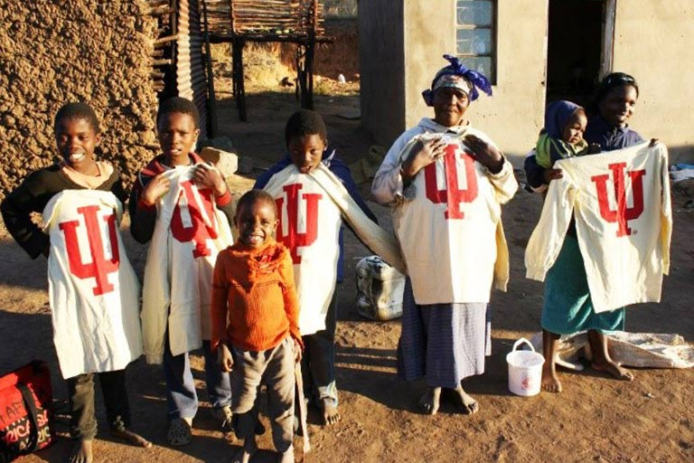 Children and adults in Swaziland pose with IU shirts.