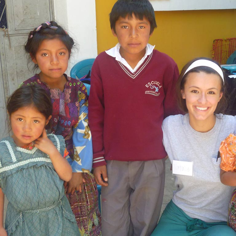 An IU nursing student poses with children in Guatemala.